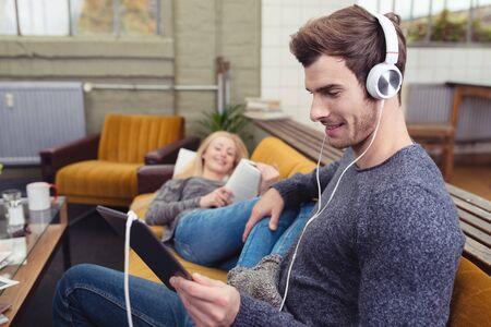 downloaded: Man sitting listening to music on stereo headphones while relaxing at home on the sofa with his wife checking his downloaded tunes on a tablet Stock Photo