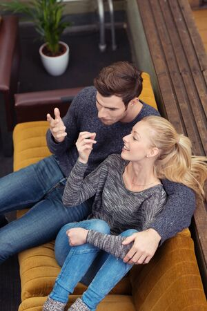 secondhand: Young couple having an animated discussion gesturing with their hands as they relax in a close embrace on a couch at home, view from above Stock Photo