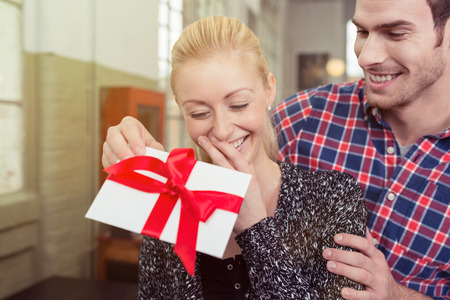 approaches: Young man surprising his sweetheart with a gift tied in a large red bow for Valentines Day as he approaches her from behind in an intimate embrace