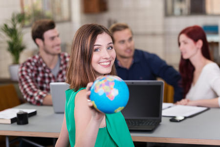 Close up Young Pretty Smiling Woman Showing Small Globe at the Camera While Having a Meeting at the Table. Banco de Imagens