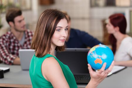 executive courses: Young businesswoman sitting in the office daydreaming of a vacation holding a globe in her hand as she plans her destinations Stock Photo