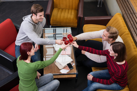 sit around: Group of friends toasting with red wine clinking their glasses as they sit around a coffee table celebrating , high angle view Stock Photo