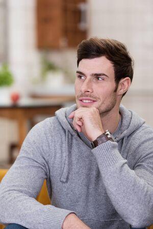 emphasising: Close up Splendida uomo in grigio manica lunga seduta sul divano con la mano sul mento, Sottolineando Sognare ad occhi aperti.