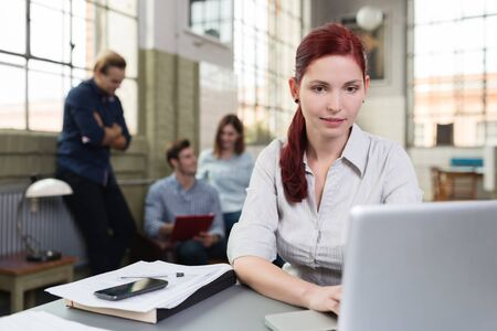 start up: Young woman working in a busy office sitting at a desk typing on her laptop computer while her colleagues hold a meeting in the background
