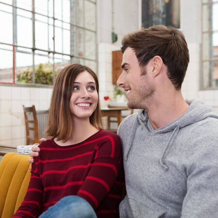 casual fashion: Close up Smiling Young Sweet Couple Wearing Casual Fashion Clothing Looking Each Other While Resting on the Sofa.