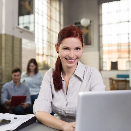 unconventionally: Close up Pretty Smiling Woman with Long Burgundy Hair in Off White Blouse Sitting at Worktable with Laptop Computer