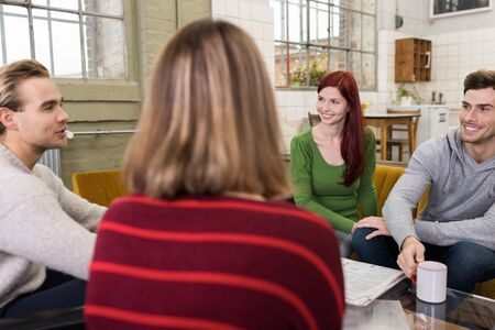 Circle of Young Adult White Friends Talking Happy Topics at the Lounge Room During their Free Time. photo