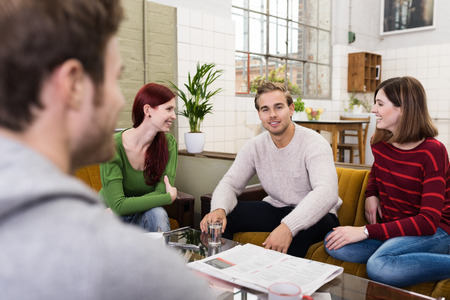 chat group: Group of Young White Friends Relaxing at the Living Room Area While Sharing Happy Moments. Stock Photo