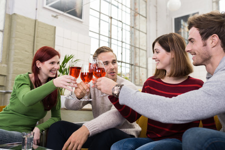 Happy Young White Friends in Casual Long Sleeve T-Shirts Tossing a Glass of Drink While Resting at Living Room photo