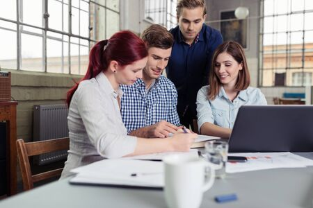 conversation: College Friends Having Serious Group Study at the Table Inside the Office. Stock Photo