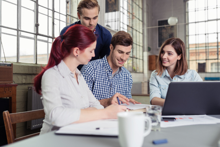 unconventionally: Young People Discussing While Having a Group Study at the Table Inside the Office. Stock Photo