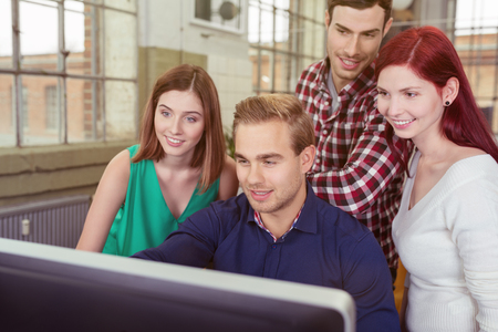clustered: Smiling group of young people in the office clustered around a young man at a desktop computer reading the information on the screen