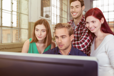 Informal young business team anxiously watching the success of their project as they stand grouped around a large screen desktop computer Stock Photo