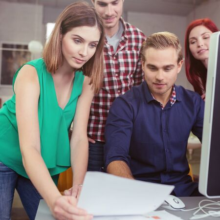 eagerly: Young businesswoman presenting documents to a handsome young man seated at a computer watched eagerly by two colleagues