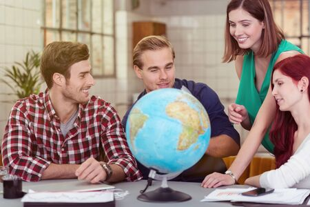 Group of Young Happy Friends Looking at the Globe on Top of the Table photo