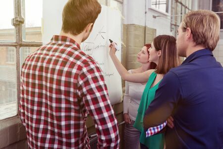 unconventionally: Group of Young White Friends Discussing Project Plans at the White Board. Stock Photo