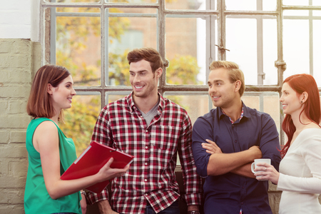 Group of Happy Young Friends Talking Near the Glass Window of the Building During Break Time. Stock Photo