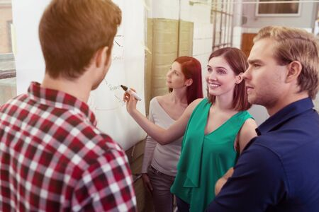 Group of Young Friends Discussing Project Plans Written on a White White Poster Paper Hanging on the Wall photo