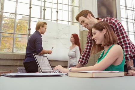 personas ayudando: Dos compañeros de trabajo en una concurrida oficina moderna con jóvenes motivados que trabajan juntos en un ordenador portátil sonriendo mientras leen la información en la pantalla Foto de archivo