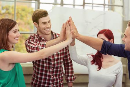 ležérní: Usměvavé obchodní tým dává vysokou pětky s rukama nad hlavou, jak se slaví svůj úspěch v kanceláři koncepční týmové práce