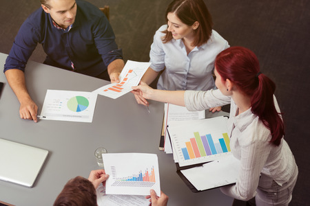 sit around: Young business team working on analytical graphs as they sit grouped around a table, high angle view showing the colorful charts