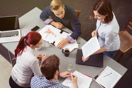 competencias laborales: Vista aérea de Jóvenes Empresarios Amigos discutir el proyecto en la mesa de trabajo.