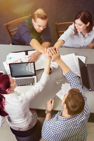 Group of Young Friends Having a Business Meeting at the Table with Laptops and Documents While Holding Their Hands Together at Center, Captured in Aerial View Stock Photo