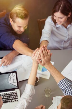 five people: Close up Aerial View of Group of Friends Holding Hands Together at the Center While Having a Meeting at the Table.