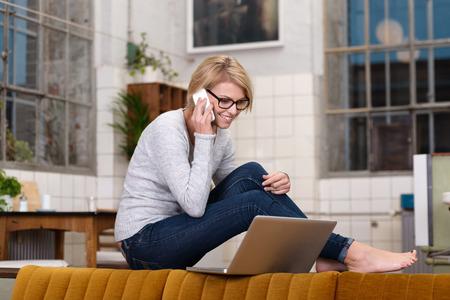 Mladá žena pracující z domova sedí bosa na kuchyňské lince chatování na její mobil při čtení obrazovky svém notebooku vyváženou na opěradlo pohovky