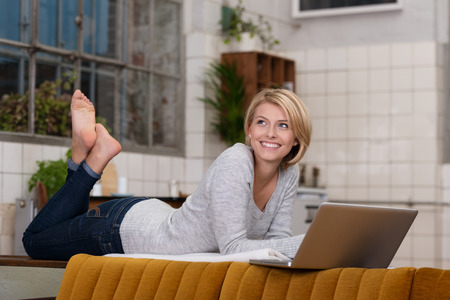 the laying: Smiling pretty woman relaxing with her laptop lying on the dividing wall in her living room with her bare feet in the air smiling as she looks to the side Stock Photo