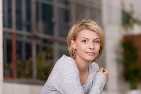Close-up mooie blonde vrouw draagt grijze shirt met lange mouwen met een arm Crossing op de borst deel, Kijkend naar de camera.