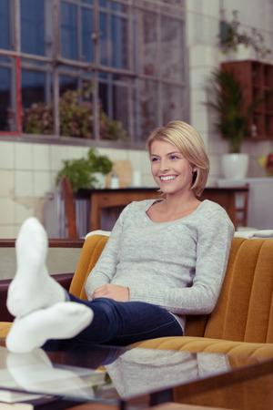 Glimlachend aantrekkelijke jonge vrouw ontspannen thuis op een comfortabele bank met haar schoenen uit en voeten op de salontafel