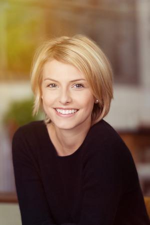 Sluit omhoog Portret van een vrij Glimlachende Vrouw met Kort Blond Haar, die een Toevallig Zwart Overhemd dragen, die de Camera bekijken. Stockfoto