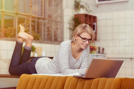 Gelukkig blonde vrouw liggend op haar buik op de tafel achter de bank tijdens het gebruik van haar laptop computer.
