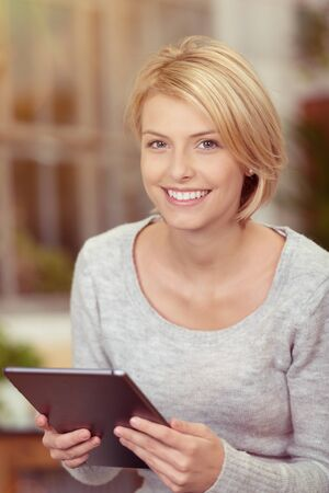 blonde females: Close up Pretty Smiling Blond Woman in a Gray Long Sleeve Shirt Holding a Tablet Computer While Looking at the Camera.