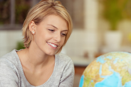 Happy young woman planning a summer vacation sitting in front of a world globe smiling in anticipation photo
