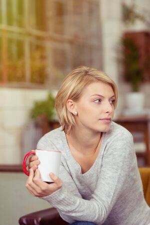 observant: Observant young woman with a cup of coffee cradled in her hands sitting staring off to the right of the frame Stock Photo