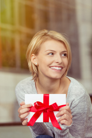 christmas bonus: Joyful woman holding a Valentines or birthday gift tied with a large red bow looking off to the side with a beaming smile