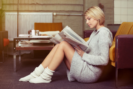 Young Blond Woman Sitting on the Floor While Leaning on Sofa and Reading a Newspaper Seriously.