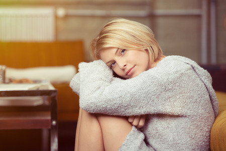 sweater girl: Serious depressed young woman relaxing at home with her head resting on her drawn up knees looking at the camera Stock Photo