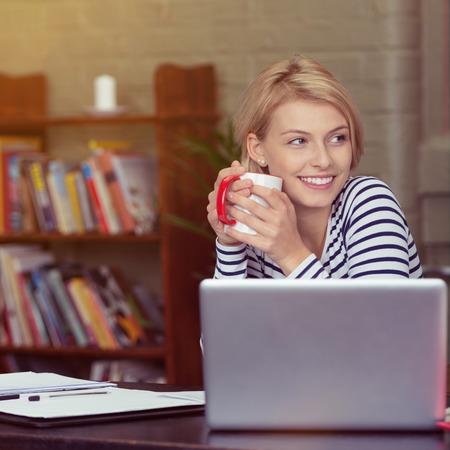 trabjando en casa: Mujer joven que toma un descanso para tomar café Feliz sonriente como ella se sienta en su computadora portátil de trabajo desde una oficina en casa con estantería