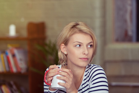 clasping: Pretty young woman relaxing with a cup of coffee sitting clasping it in her hands and looking off to the side with a dreamy expression