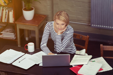 Attractive businesswoman surrounded by paperwork as she sits at her desk working on a laptop computer, high angle view