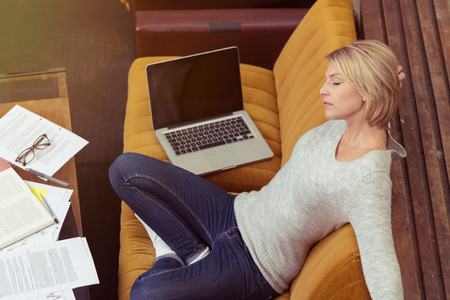 tired eyes: Aerial View of Tired Blond Woman Leaning on Dark Yellow Sofa, with Laptop Computer on the Side, In Front of Documents on a Table. Stock Photo