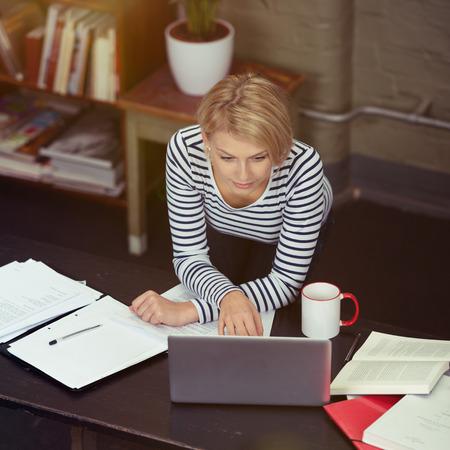 rubia: Mujer bastante rubia apoyado en la mesa mientras que trabaja en su computadora port�til con documentos, libros y taza en los lados.