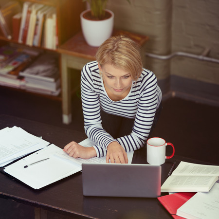 online learning: Pretty Blond Woman Leaning on the Table While Working on her Laptop with Documents, Books and Coffee Mug on the Sides.