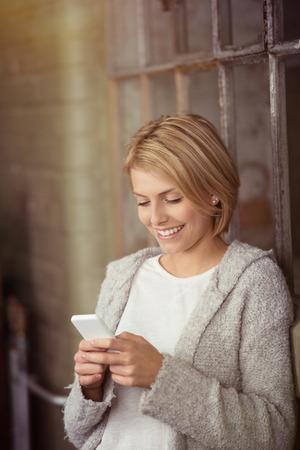 rubia: Cierre de feliz Mujer rubia joven en ropa casual ocupada con su tel�fono m�vil mientras se apoya en la ventana de vidrio Foto de archivo