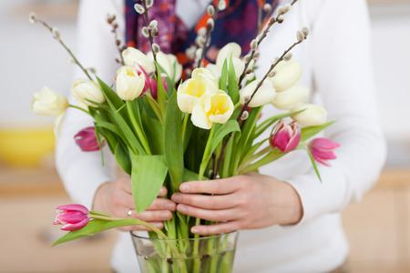 Woman arranges spring flower bouquet in a vase
