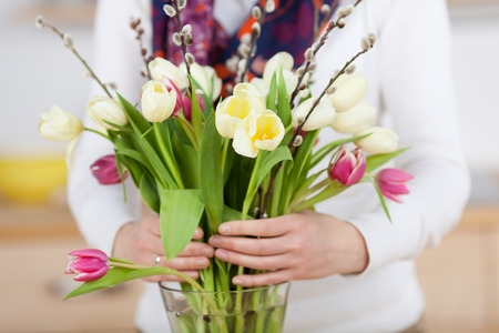 pink tulips: Woman arranges spring flower bouquet in a vase
