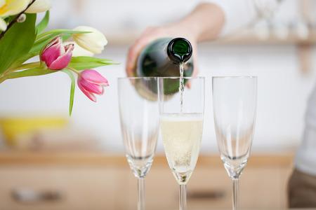 botella champagne: Verter el champán en copas de pie sobre la mesa